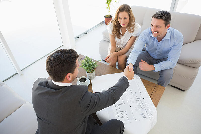 High angle view of a smiling young couple in meeting with a financial adviser at home