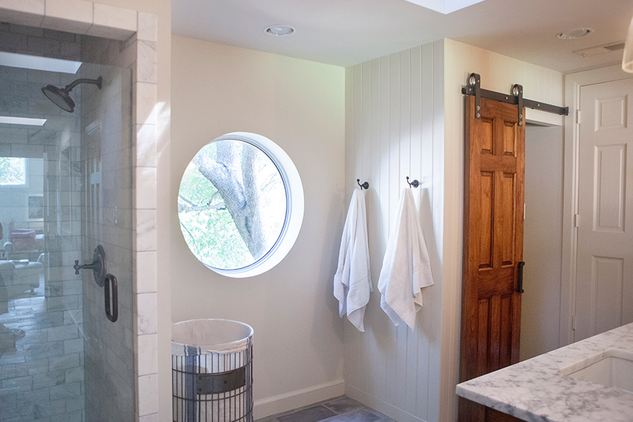Bathroom Design (Custom Texas Homes): Pine Barn Door and Oval Window in Custom Bath