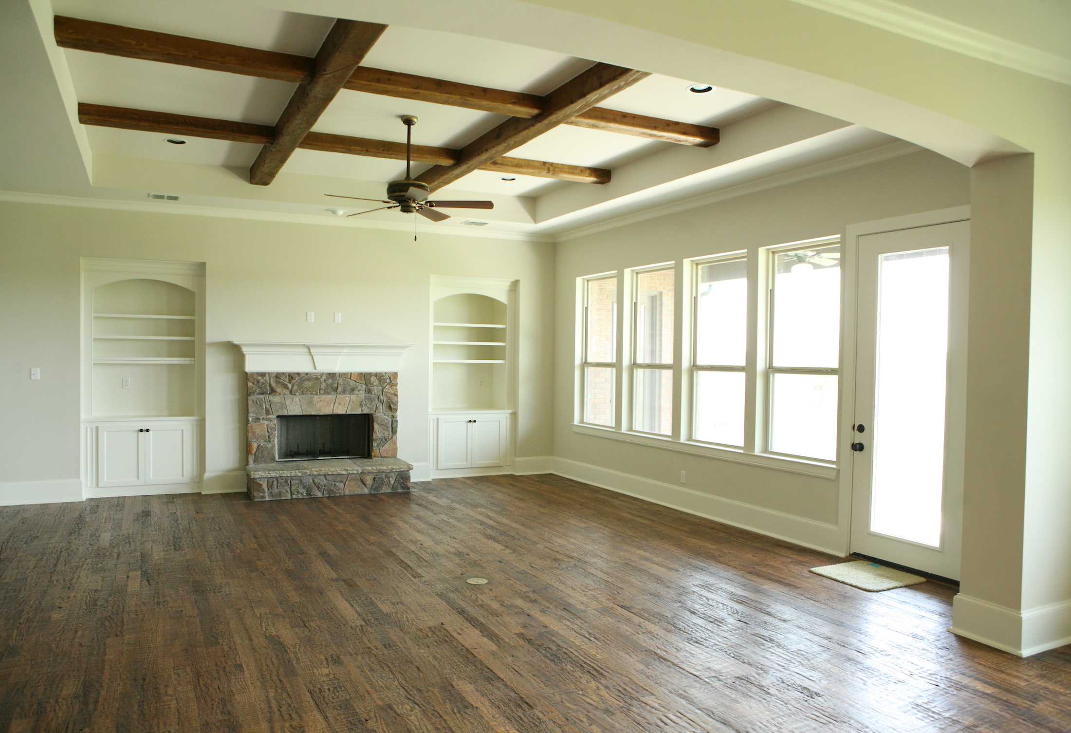 Living Room Design (Texas Homes): saddle creek family room with oak floors and beams and stone fireplace